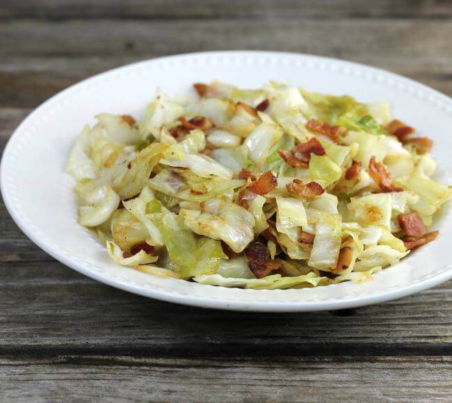 Side view of fried cabbage in a white bowl.