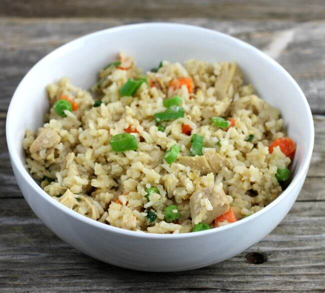 Fried rice in a white bowl with green onions on top