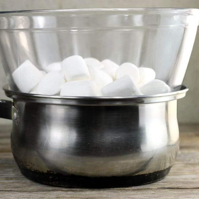 Double boiler with marshmallow in the bowl.