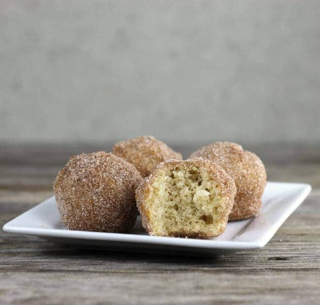 Muffins on a plate with one with a bite out of it.