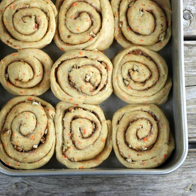 Unbaked sweet rolls in a baking pan.