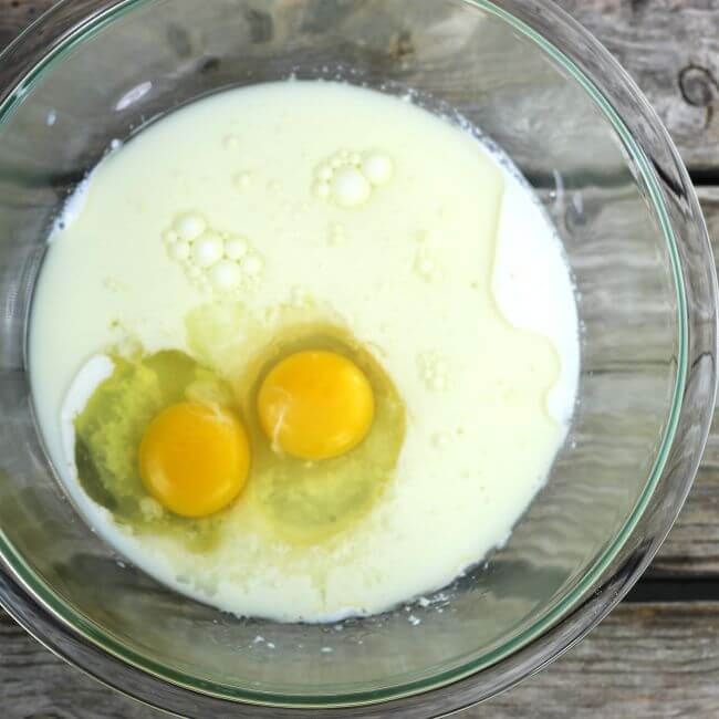 Eggs, milk, and oil in a glass bowl.