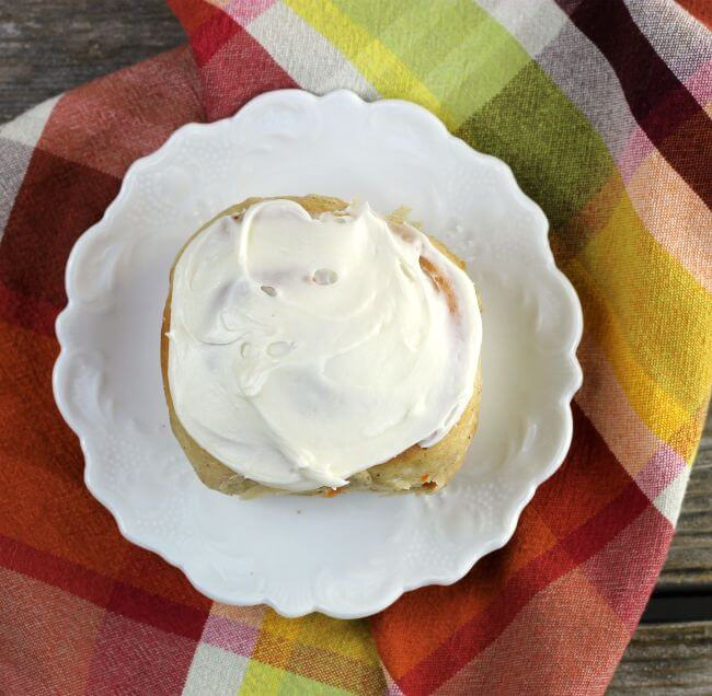 Looking down at a sweet roll on a white plate with a plaid napkin under the plate.