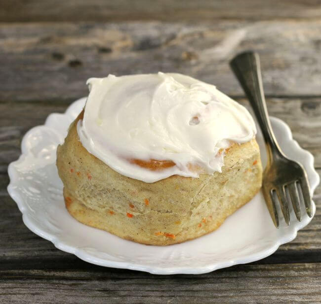 Side angle view of a sweet roll with a fork on a white plate.