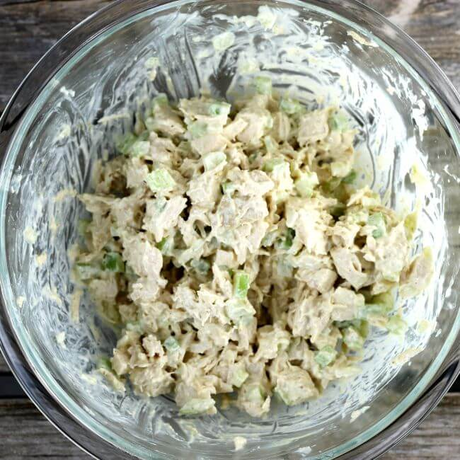 Chicken salad mixed together in a glass bowl.