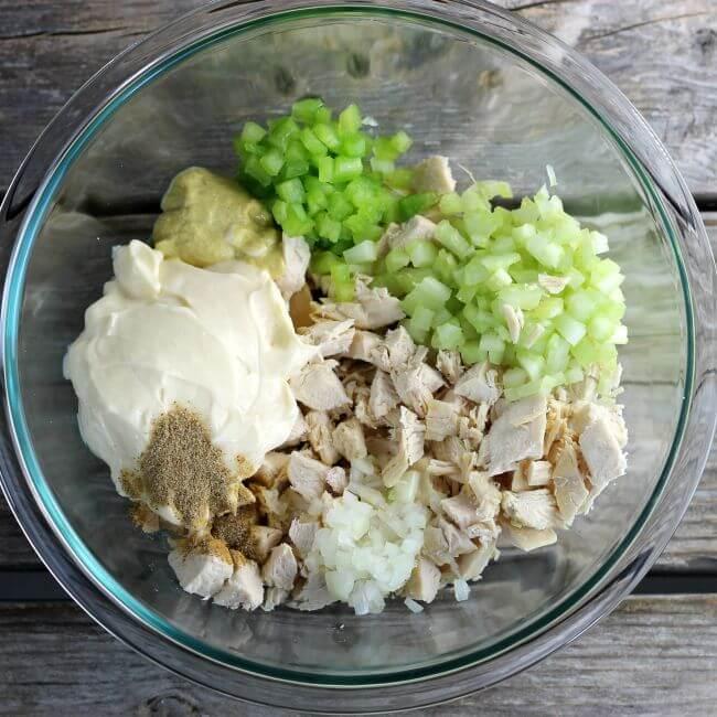 Chicken, veggies, seasoning, Dijon mustard, and mayo in a glass bowl.