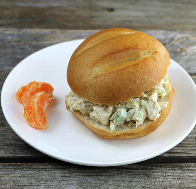 Side angle view of a chicken salad sandwich on a white plate.