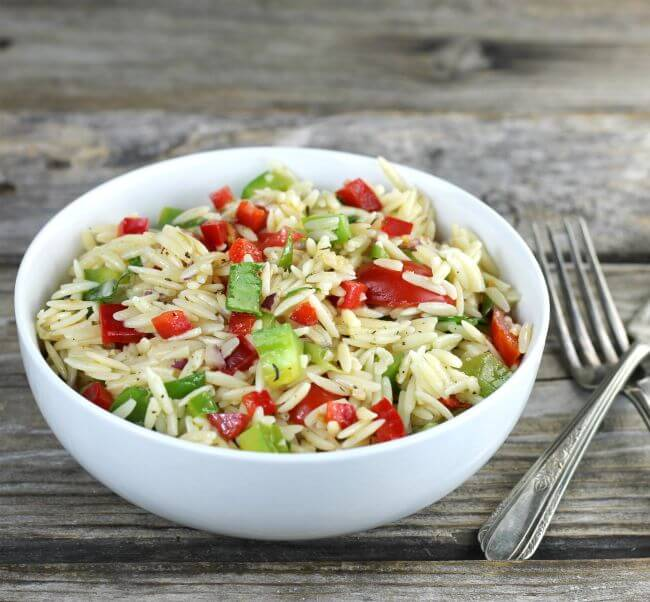 Side angle view of orzo pasta salad in a white bowl.