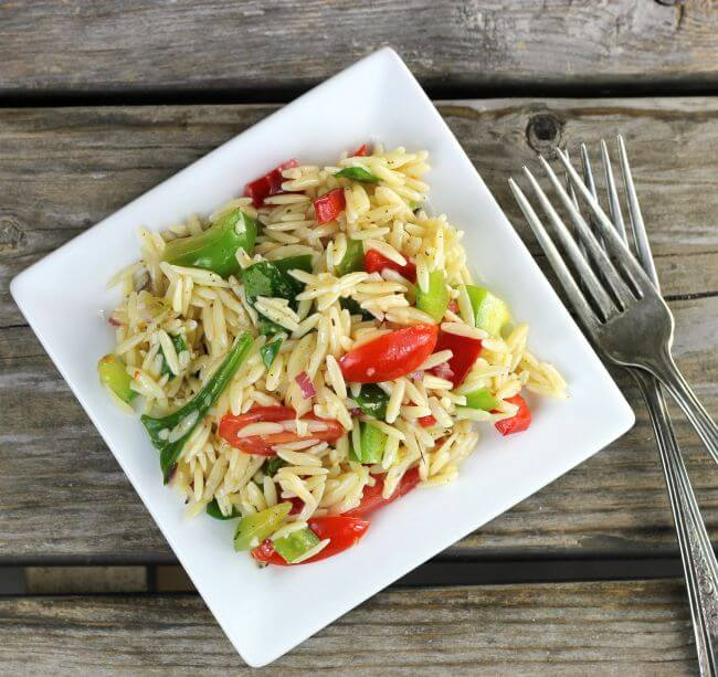 Over looking orzo pasta salad on a white square plate.