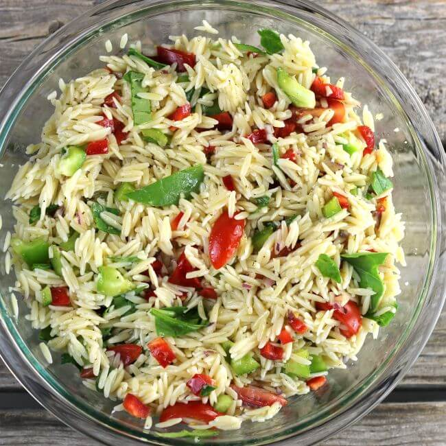 Orzo pasta salad in a glass bowl.