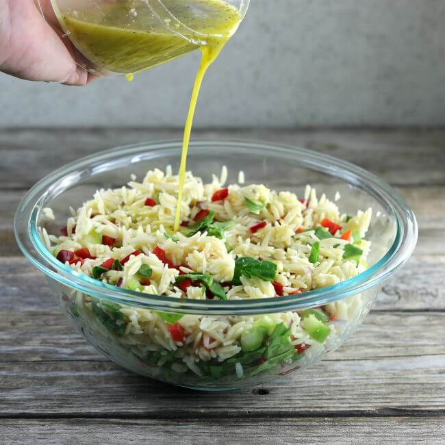 Pouring dressing on the orzo salad.