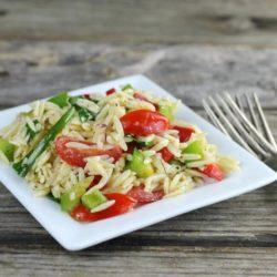 Side angle view of orzo salad on a square white plate.