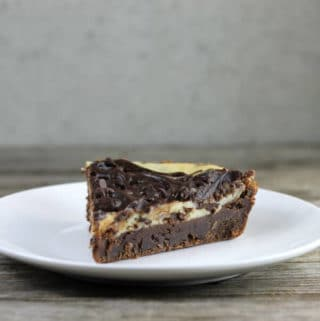 Side angle view of a piece of brownie pie on a white plate.