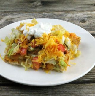 Side angle view of taco pizza with sour cream on top.