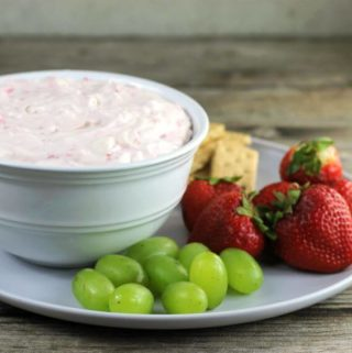 Side view of a bowl of cheesecake dip on a plate with grapes and strawberries.