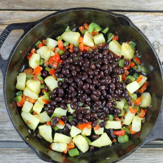 Black beans are added to the vegetables in the skillet.