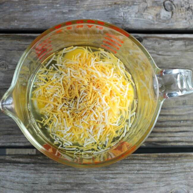 Eggs, cheese, salt, and pepper are added to a large measuring cup.