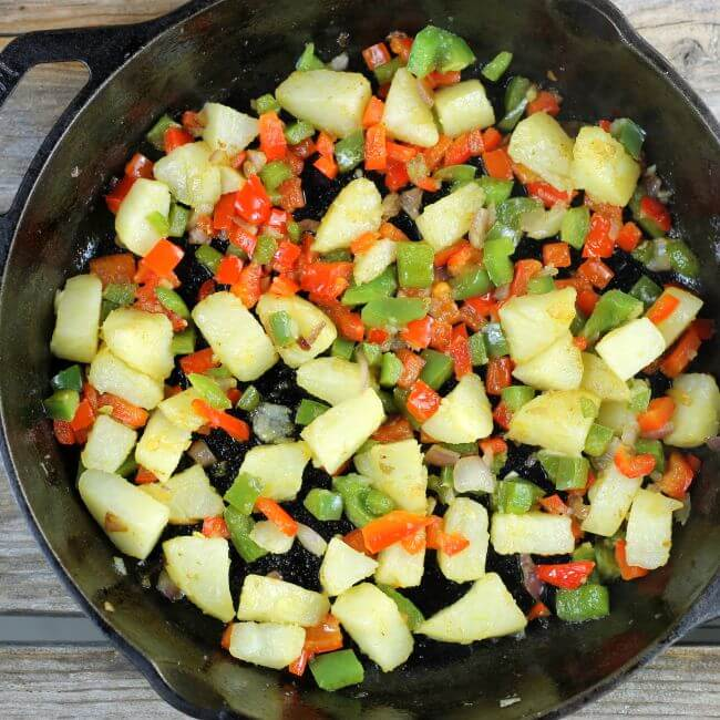 Potatoes, peppers, and onions in a cast-iron skillet.