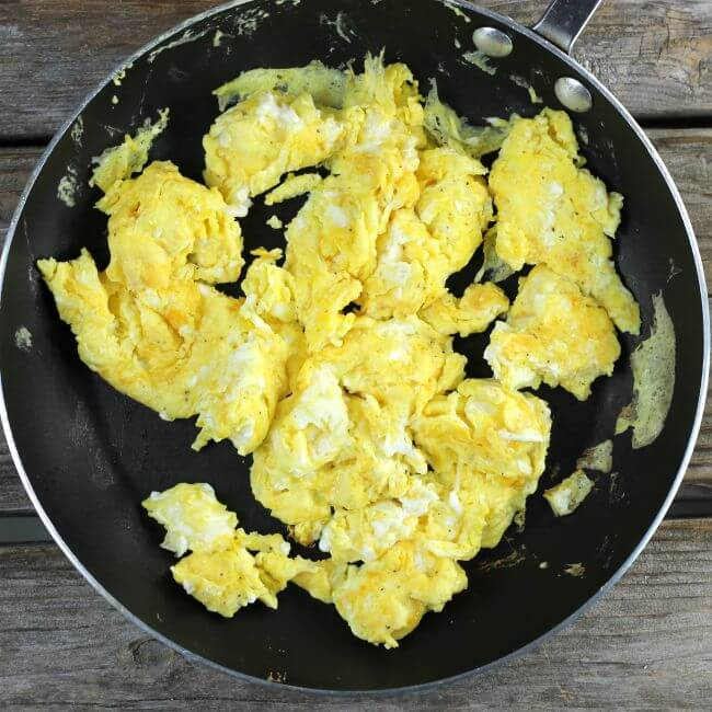 The scrambled eggs are cooked in the skillet.