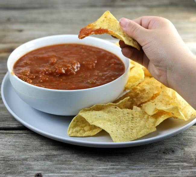 Someone holding chip with salsa on it.