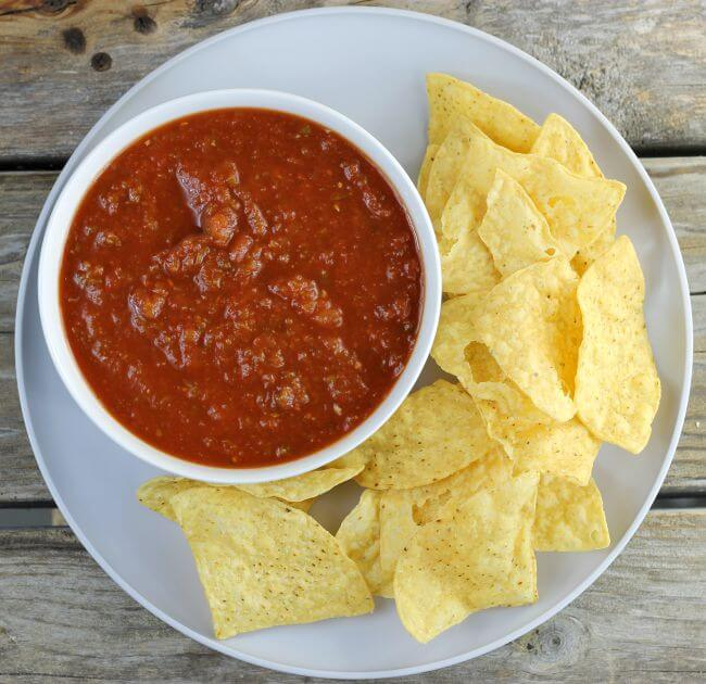 Looking down at a bowl of salsa with chips on a gray plate.