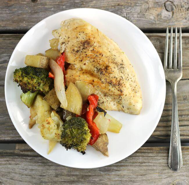Looking down at a plate that has a chicken breast and vegetables with a fork on the side.
