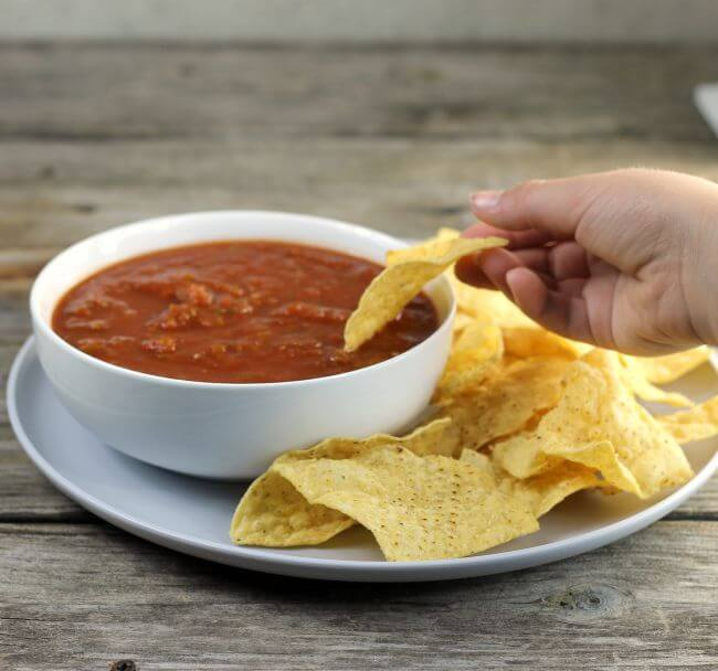 Someone dipping a chip into a bowl of salsa.