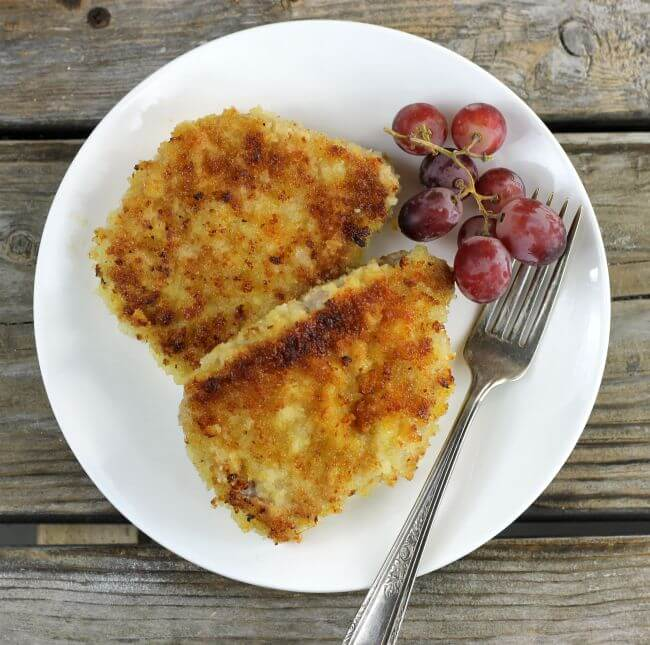Looking down at two pork chops on a white plate with grapes and a fork.