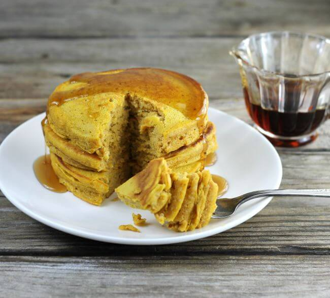 Side angle view of pancakes with a container of syrup behind the plate.