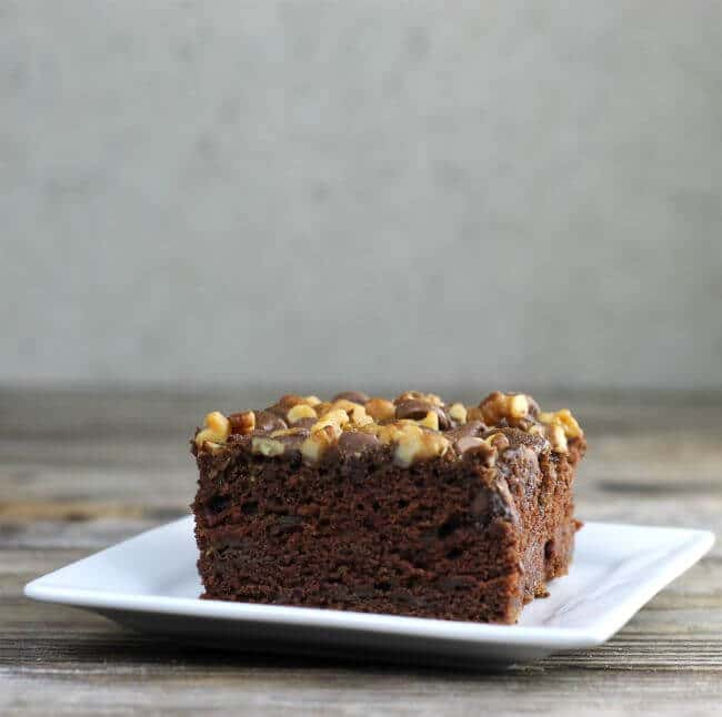 Looking at a side view of chocolate zucchini cake on a plate.