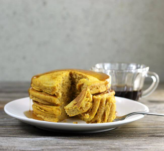 Side view of pumpkin pancakes with a few pieces of pancake on a fork.