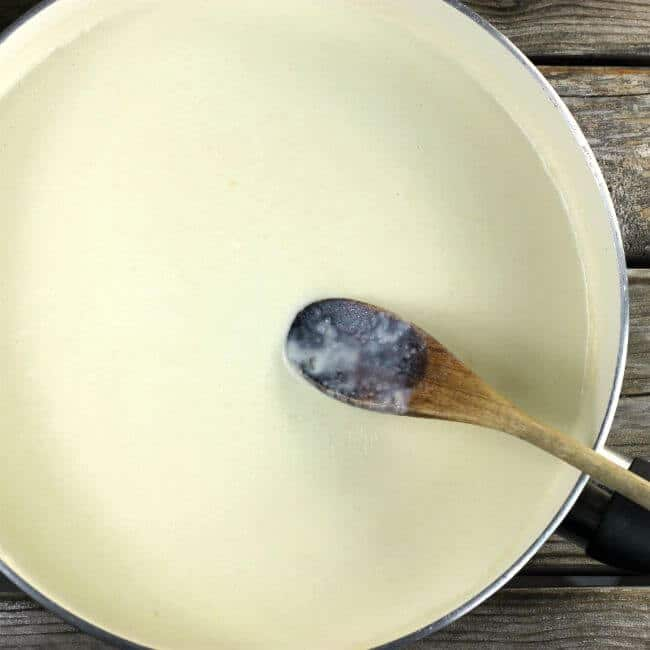 White sauce in a skillet with a spoon for mixing.