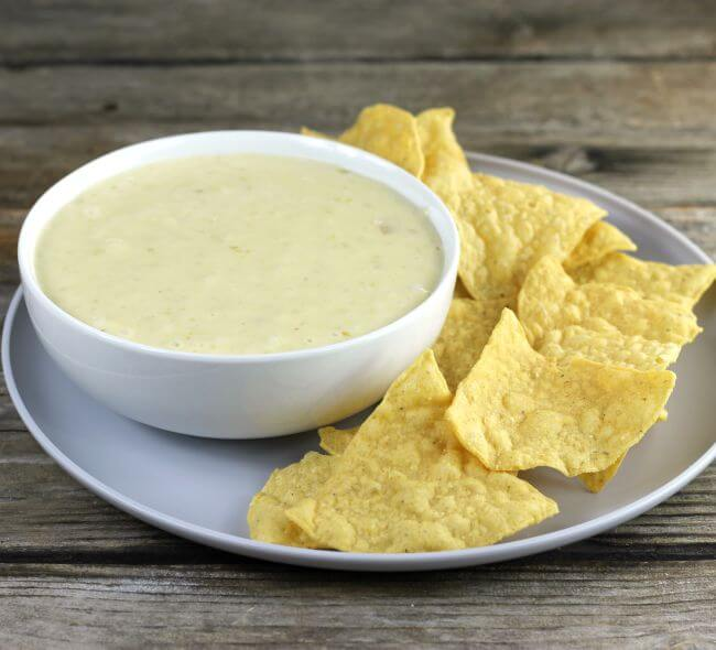Looking at a side angle view of a bowl of queso and chips.