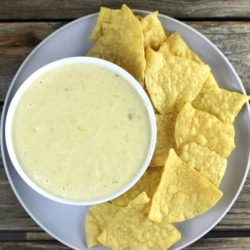 Looking down at a bowl of questo on a plate with tortilla chips.