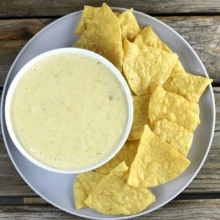 Over looking a plate with a bowl of queso with a side of chips.