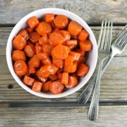 Overview of a bowl of glazed carrots with two forks on the side.