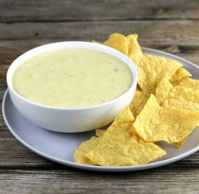 Side angle view of a bowl of queso dip with chips.