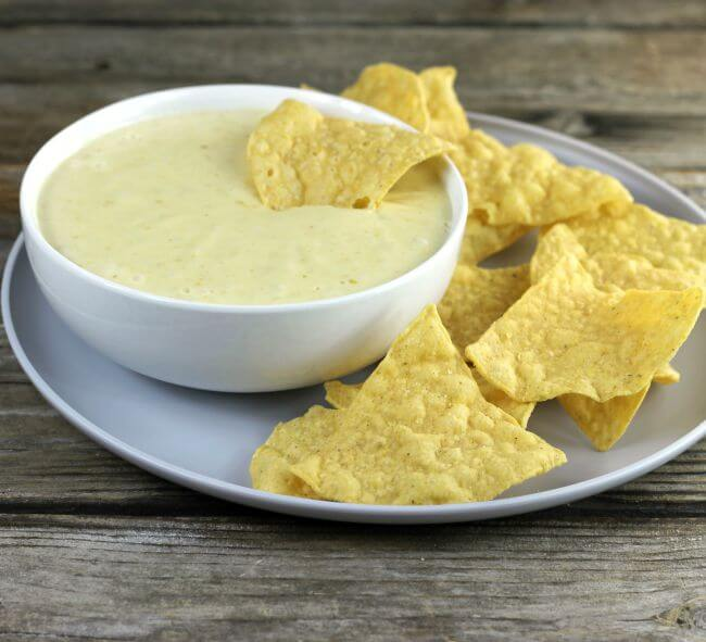 Side view of a bowl of queso dip with a chip stuck in the dip and other chips on the side.