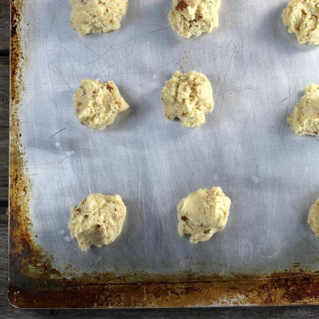 Dropped cookie dough is on a baking sheet.