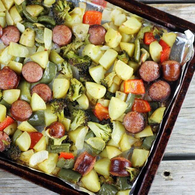 Roasted vegetables and sausage on a baking sheet.