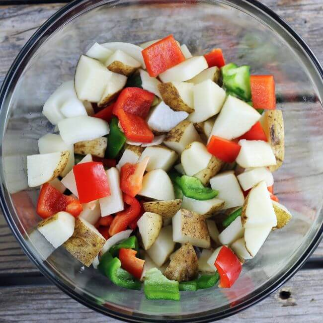 A bowl of cubed potatoes, peppers, and onions.