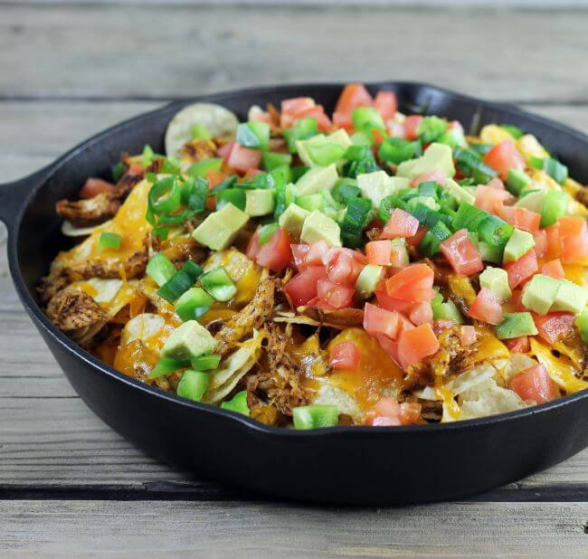 A side view of chicken nachos in a cast-iron skillet.