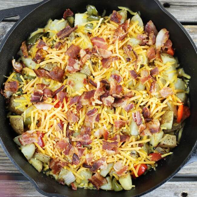 Cheese and bacon are put on top of the baked vegetables.