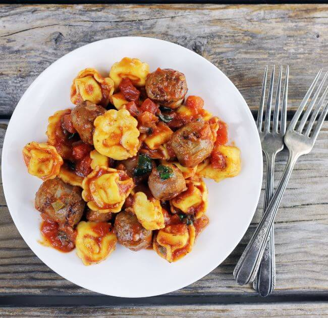 Looking down at a plate of Italian sausage and tortellini with forks on the side.