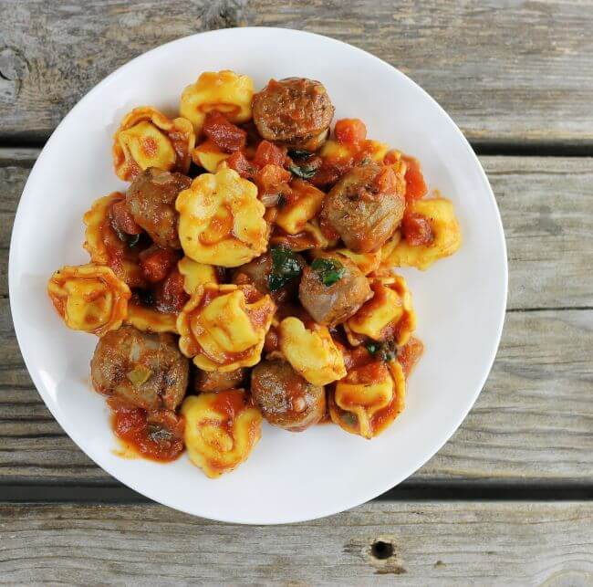 Over looking a plate loaded with Italian sausage and tortellini.