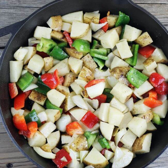 Potatoes, peppers, and onion are added to a skillet.