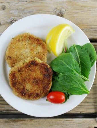 Looking down at a couple of tuna cakes with lettuce and a lemon wedge on the side.