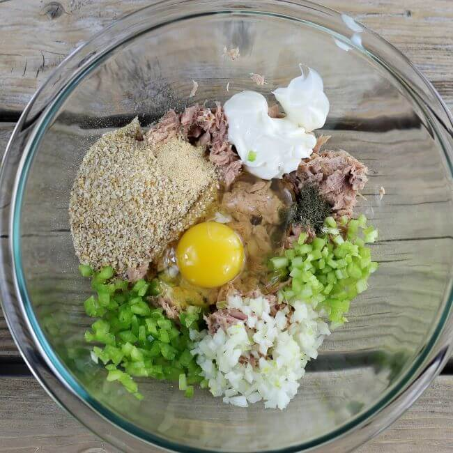 Tuna, bread crumbs, egg, celery, onion, green pepper, and mayo in a large glass bowl.